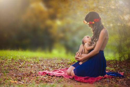 mujer sosteniendo a un bebé en brazos y dándole pecho