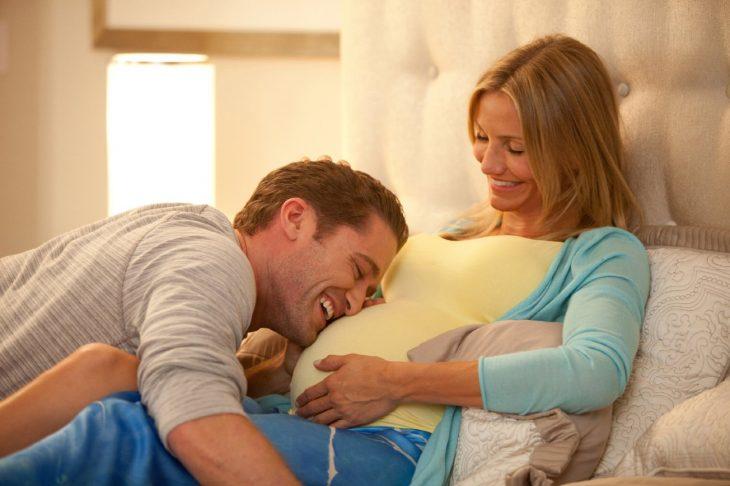 hombre besando la panza de embarazada de una mujer que esta recargada en una cama