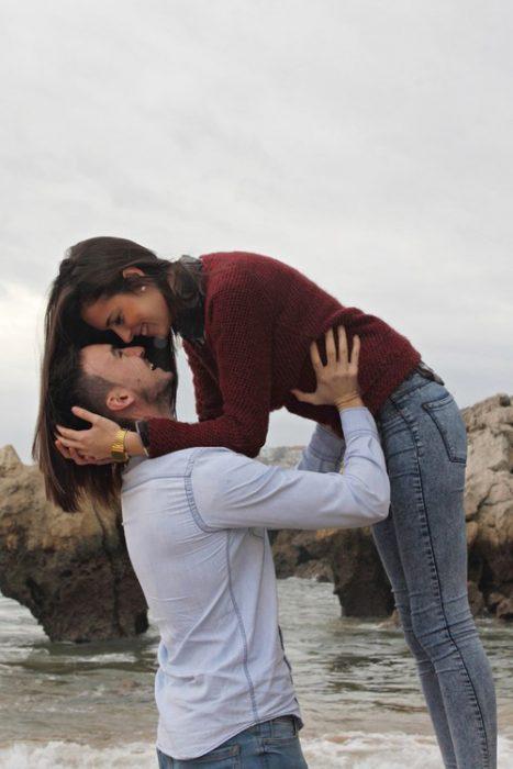 hombre cargando a una mujer de la cintura y levantándola