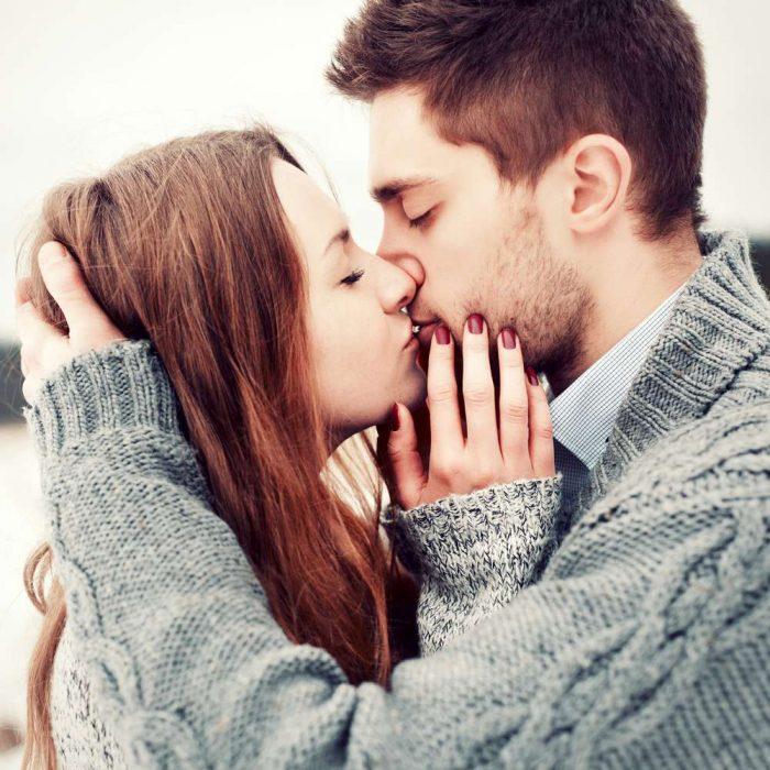 pareja de novios abrazados besándose y tocándose la cara