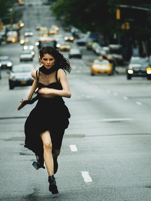 chica corriendo en medio de la carretera con vestido y botas militares