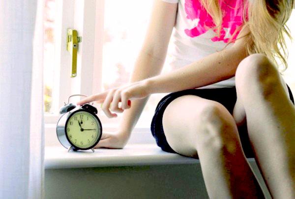 chica presionando un reloj con sus dedos