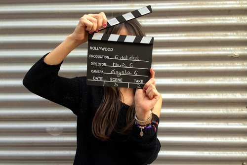 chica sosteniendo una claqueta de película en sus manos