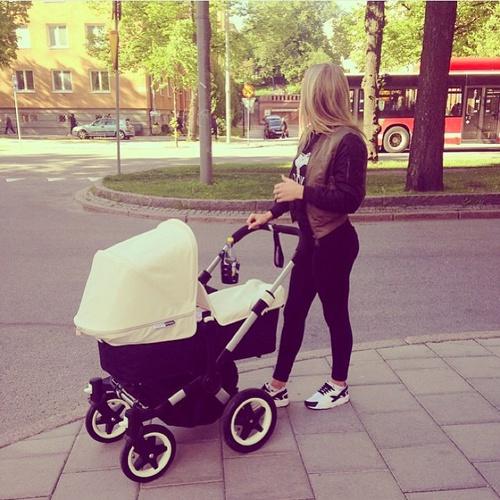 mujer empujando un cochecito de bebé