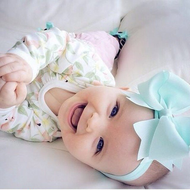 bebé recostada en una cama con un moño en la cabeza sonriendo