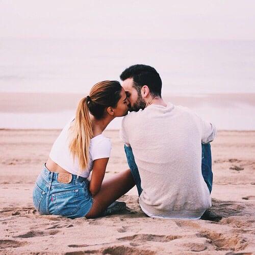 Pareja de novios sentados en la arena de la playa besándose