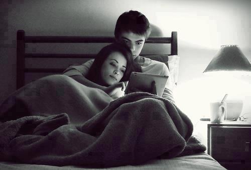 pareja de novios acostados en la cama viendo una ipad