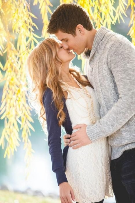 chico besando a una chica en los labios mientras la sostiene de la cintura