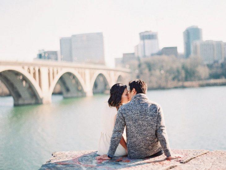 pareja de novios sentados sobre unas rocas viendo la ciudad frente a ellos