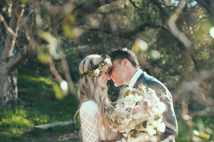 pareja de novios el día de su boda posando para una fotografía bajo un árbol