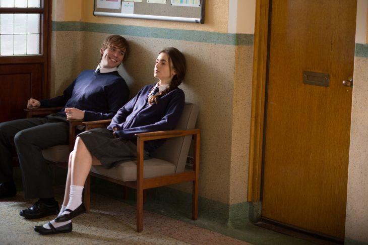 chico y chica con uniforme del colegio sentados conversando