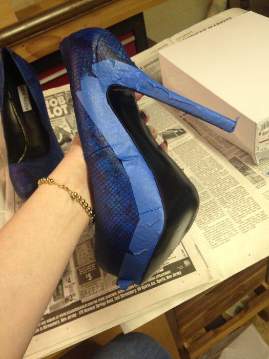 Zapatos azules cubiertos con cinta adhesiva para ser pintados