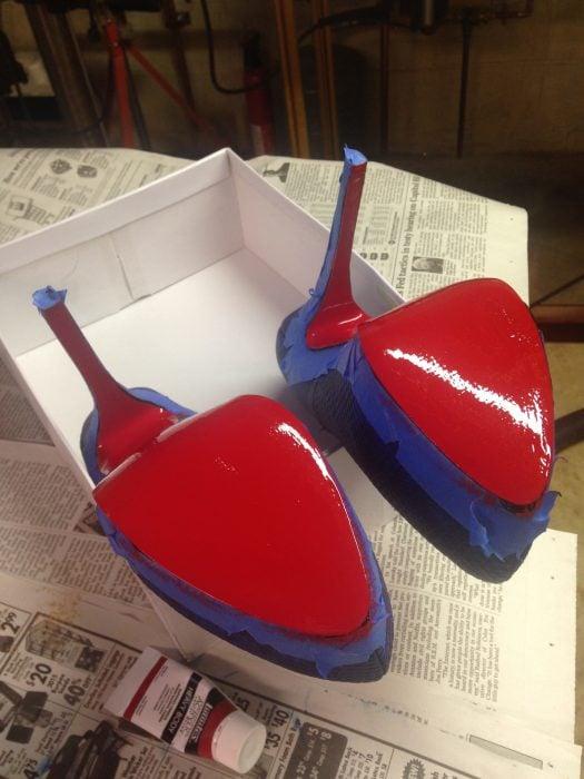 Zapatos de tacón que están siendo pintados con pintura de color roja