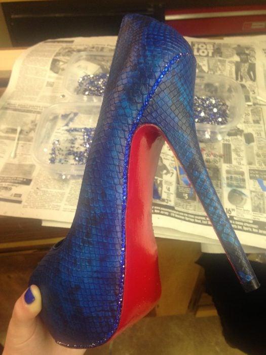 Zapatos de color azul a los que les colocan piedras