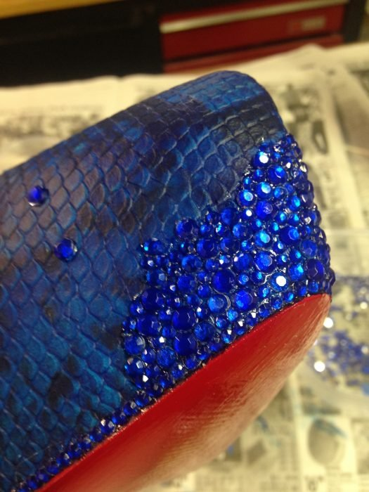 Zapatos de color azul siendo forrados con piedras una a una