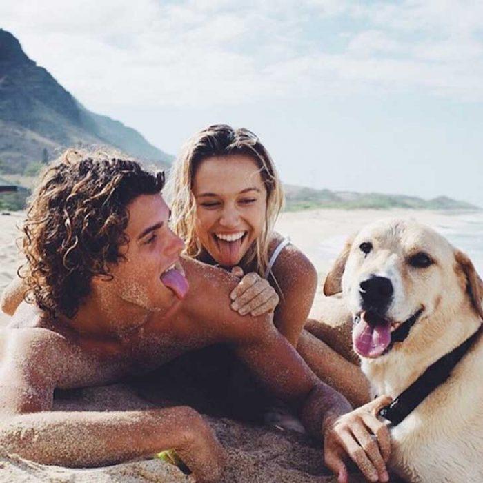 Pareja con su perro en la playa