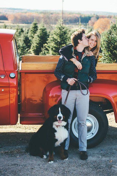 pareja recargada en una camioneta con su perra