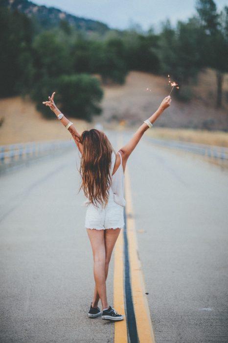 chica en una carretera levantando las manos