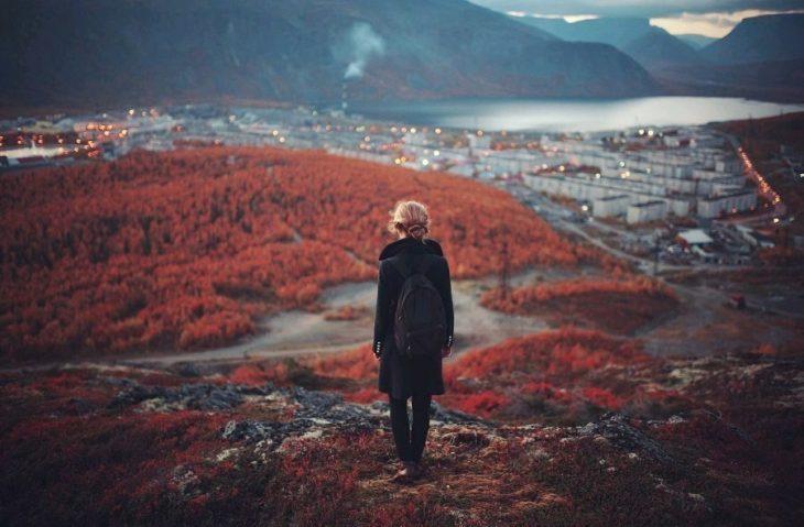 Chica parada en piedras observando la ciudad