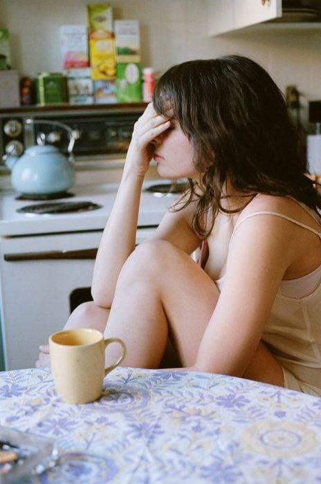 Chica tocándose la cabeza mientras toma café