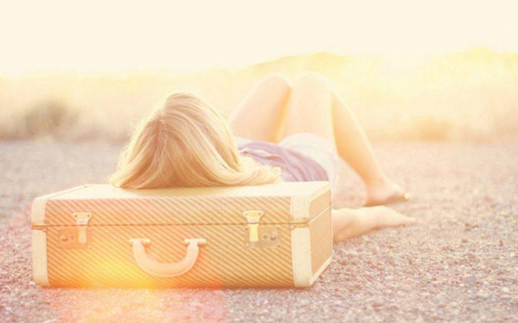 Chica acostada sobre una maleta