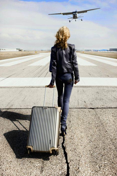 Chica con una maleta en una pista de aterrizaje