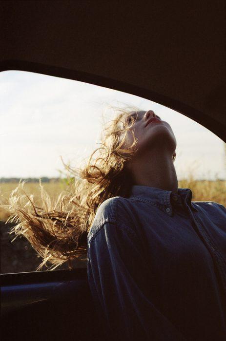 Chica con la cabeza afuera de la ventanilla de su carro