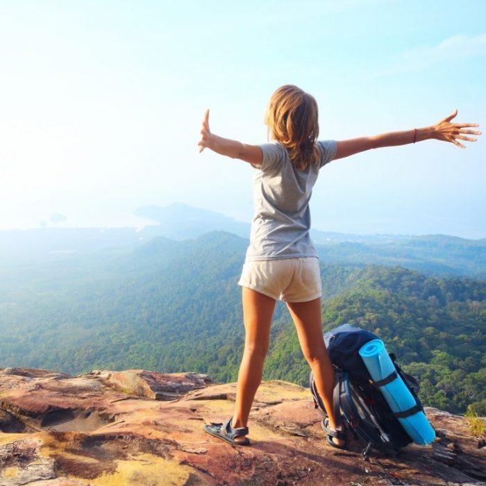 chica en una montaña con los brazos abiertos