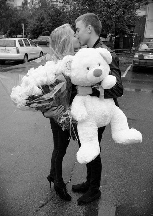 Chico regalando un oso de peluche y rosas a su novia