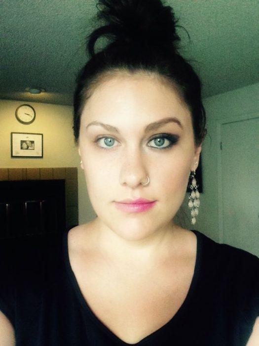Chica con un chongo y la mitad del rostro maquillado