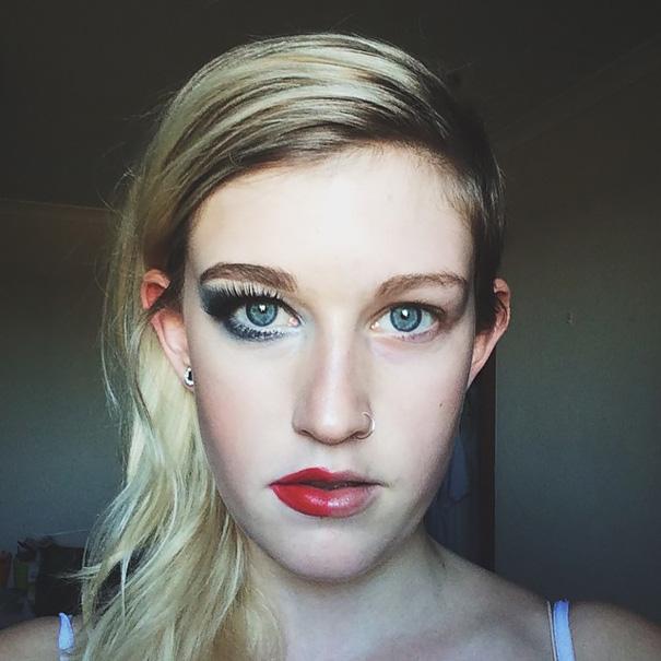 Chica rubia con la mitad de la cara maquillada en su cuarto