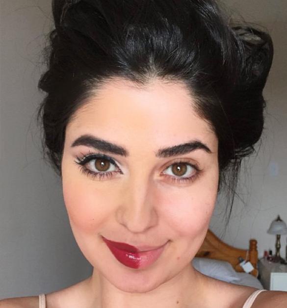 Chica con un chongo y la mitad de la cara pintada con maquillaje pintada para una selfie
