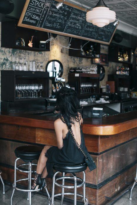 Chica sentada en una barra