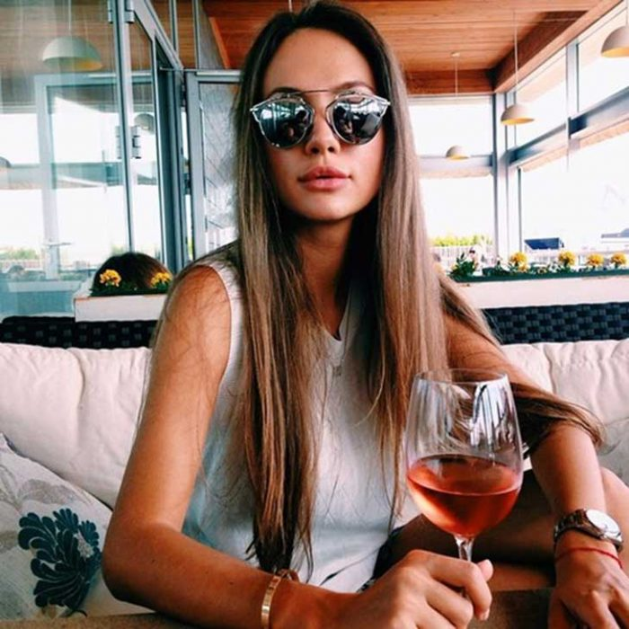 Chica tomando una copa de vino rosa