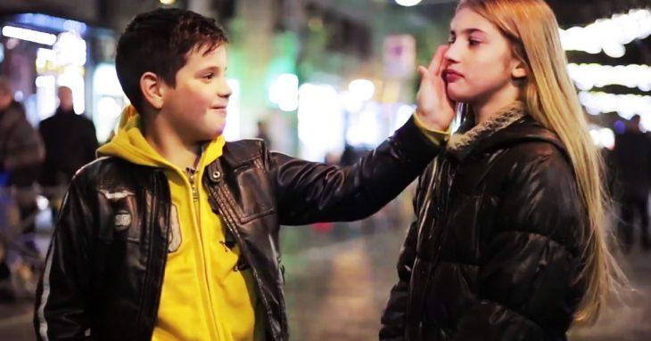 Niño con su mano puesta en la mejilla de una niña