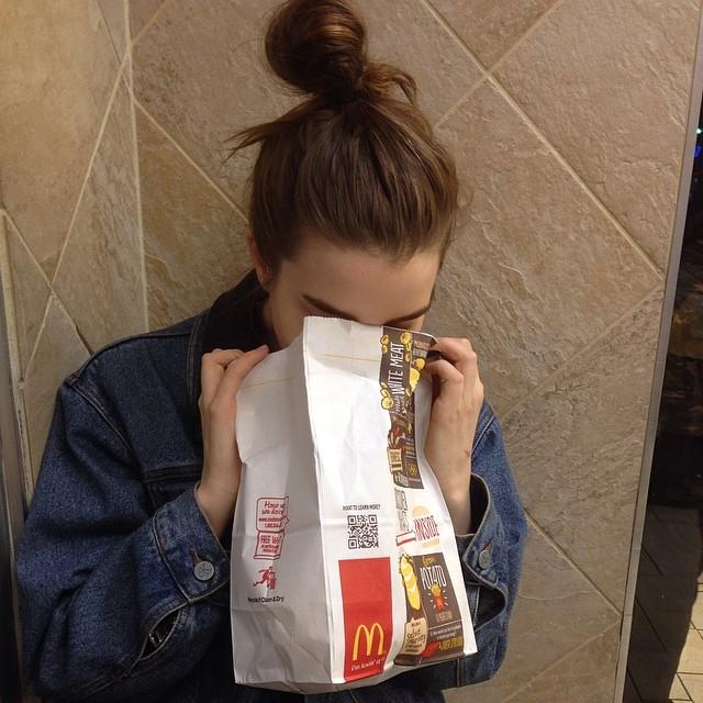 Chica con la cara dentro de una bolsa de mcdonalds