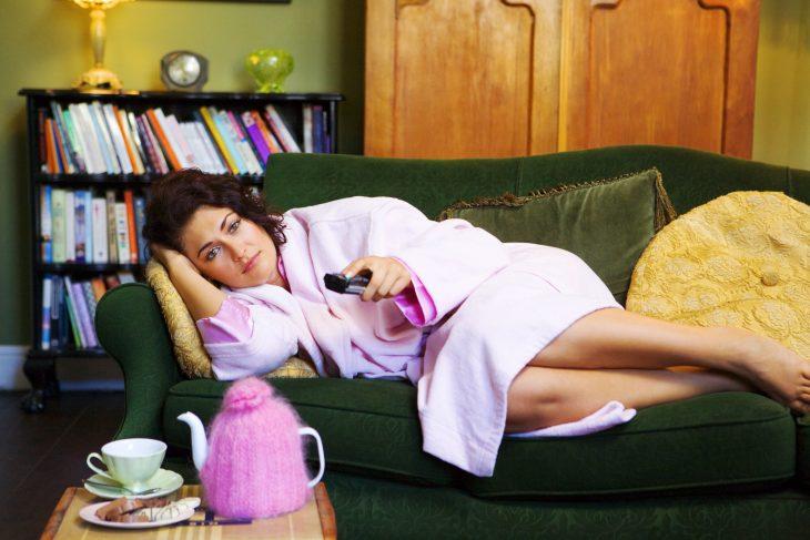 Chica con bata rosa acostada en un sillón viendo la televisión
