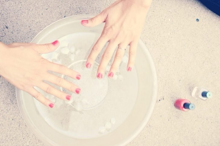 Uñas recién pintadas sumergidas en agua con hielos