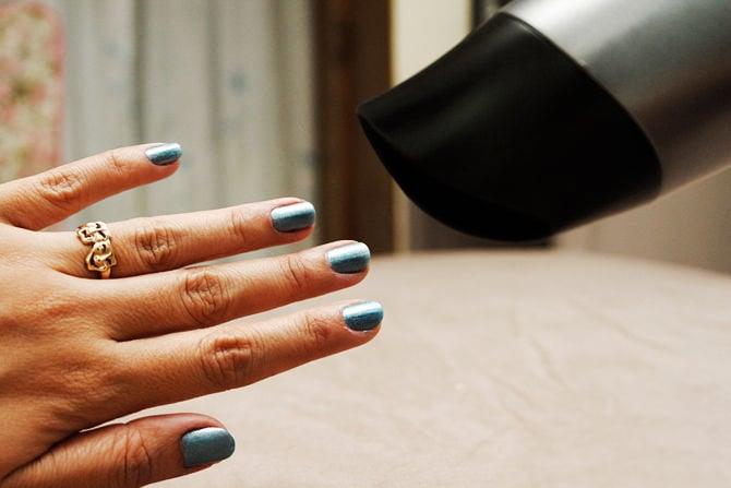 Secadora de cabello secando uñas