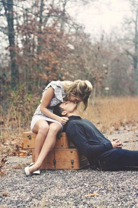 pareja de novios sentados sobre unas maletas de equipaje y besándose
