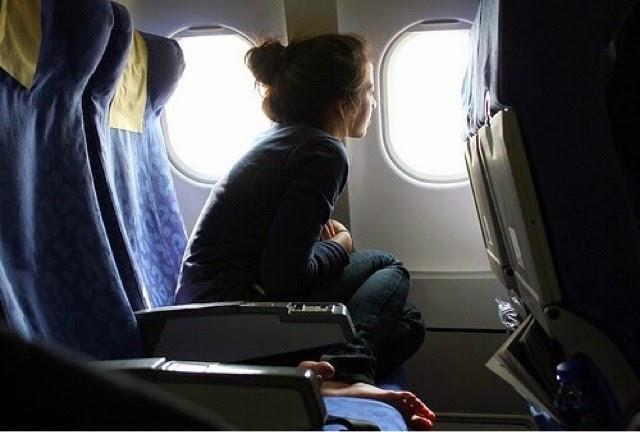 chica sentada en un avión mirando por la ventanilla