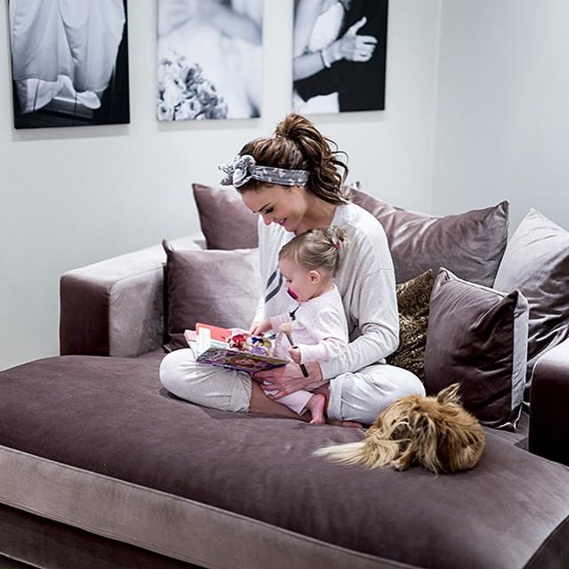mujer sentada en un sofá con una bebé en su regazo leyendo un cuento