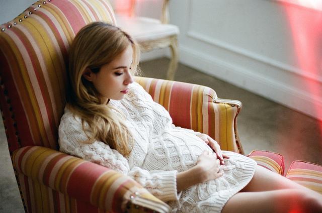 chica embarazada sentada en un sofá tocándose la pansa