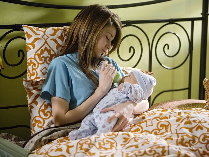 chica adolesente sentada en una cama dándole de comer a un bebé