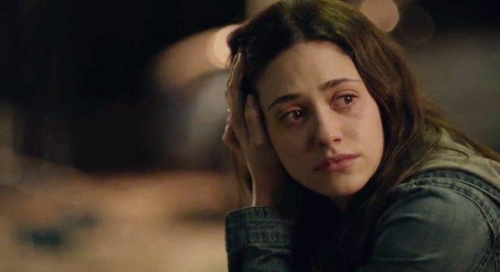 Chica de cabello corto sentada en la acera llorando