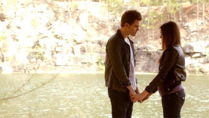 elena y stefan tomados de las manos frente a una laguna