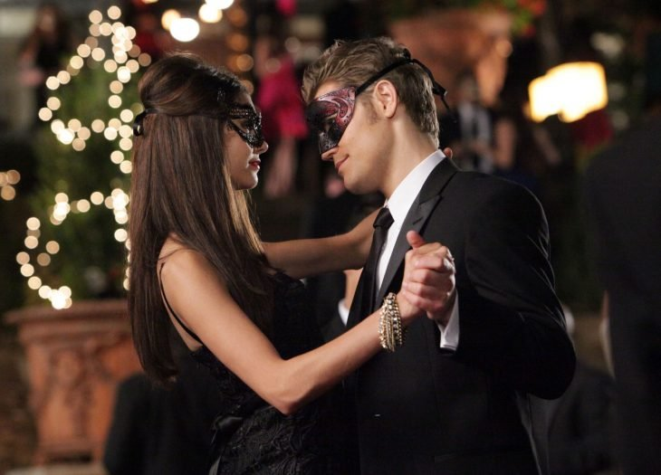elena y stefan usando mascaras en un baile