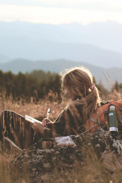 chica sentada en medio del pasto escribiendo una carta