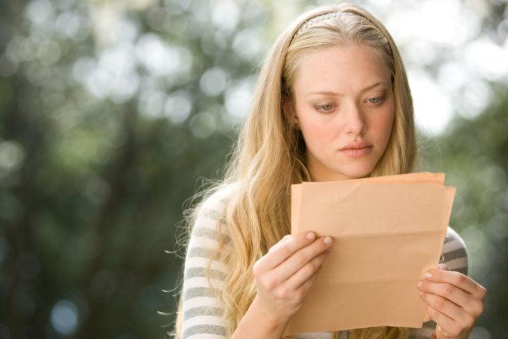 chica rubia leyendo una carta con cara de preocupación