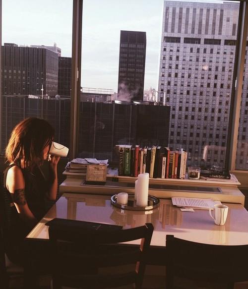 chica en una sala tomando café sola